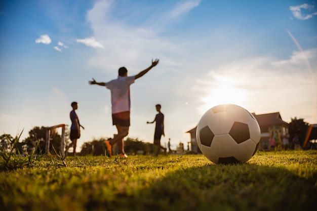 Sport d'action à l'extérieur des garçons s'amusant à jouer au football pour faire de l'exercice.