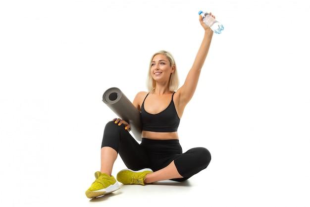 Sport caucasian girl est assis sur le sol, les jambes croisées, garde un tapis de gymnastique et une bouteille d'eau isolée
