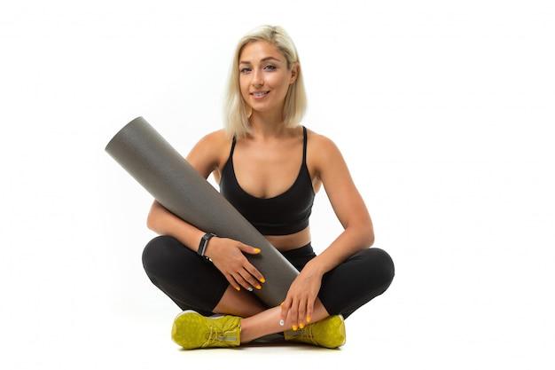Sport caucasian girl est assis sur le sol, les jambes croisées et garde un tapis de gymnastique isolé