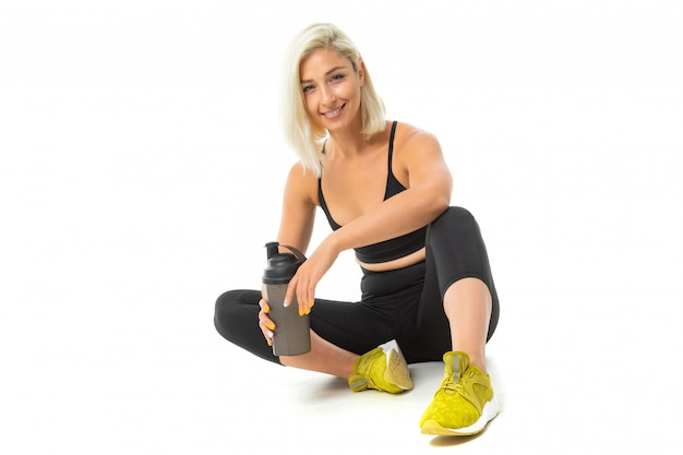 Sport caucasian girl est assis sur un sol en vêtements de sport et garder une bouteille d'eau dans ses mains
