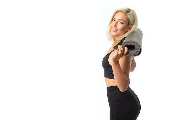 Sport caucasien girl faire du sport et garde un tapis de gymnastique dans ses mains et sourit isolé