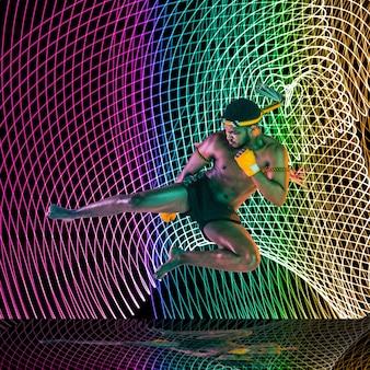 Sport créatif sur fond de ligne éclairée au néon sombre arts martiaux de l'entraînement muay thai en action