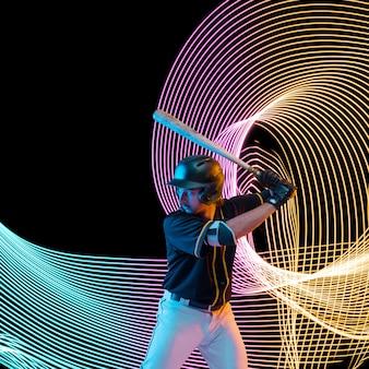 Sport créatif sur fond de ligne éclairée au néon sombre. joueur de baseball s'entraînant en action et en mouvement sur des vagues colorées. concept de passe-temps, mode de vie sain, jeunesse, action, mouvement, style moderne.