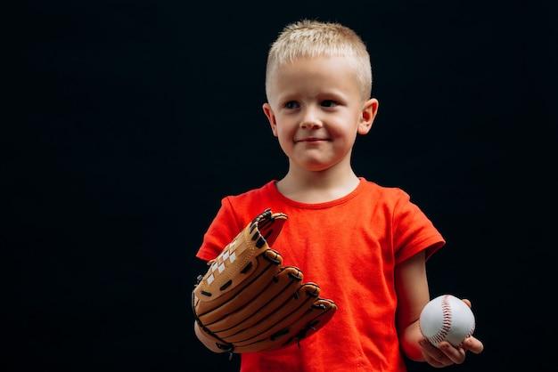 Le sport dans ma vie. taille vue portrait du joueur de baseball mignon petit garçon portant un gant spécial tenant une balle et regardant loin isolé sur fond noir