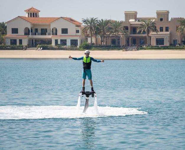 Sport extrême nautique. le gars vole au flyboard aquatique. repos extrême sur la mer.