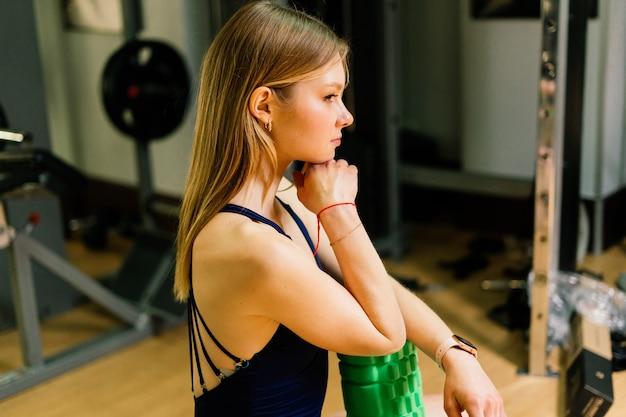 Sport féminin avec des haltères et des gants de boxeur dans la salle de sport