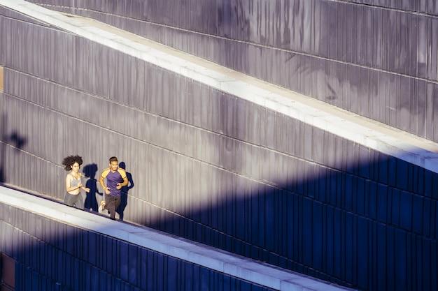 Sport femme et homme qui court sur la ville