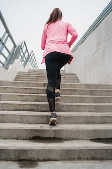 Sport femme qui court dans les escaliers.