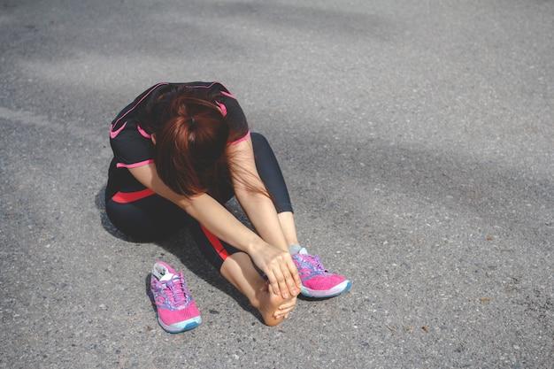 Sport femme ressentant une douleur au pied après avoir couru. blessure due au concept d'entraînement