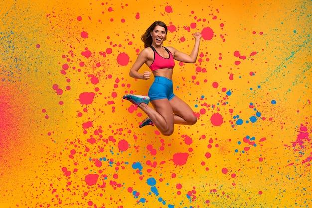 Sport femme saute. expression heureuse et joyeuse. effet spray