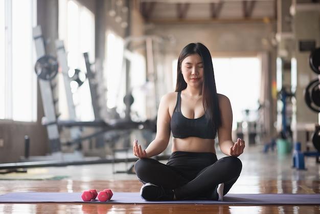 Sport femmes exercent avec haltère dans la salle de gym