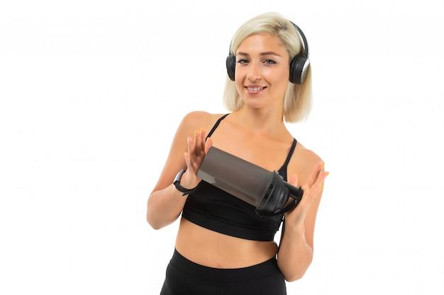 Sport fille blonde caucasienne se tient avec des écouteurs faire du sport et boit de l'eau de la bouteille de sport qu'elle montre