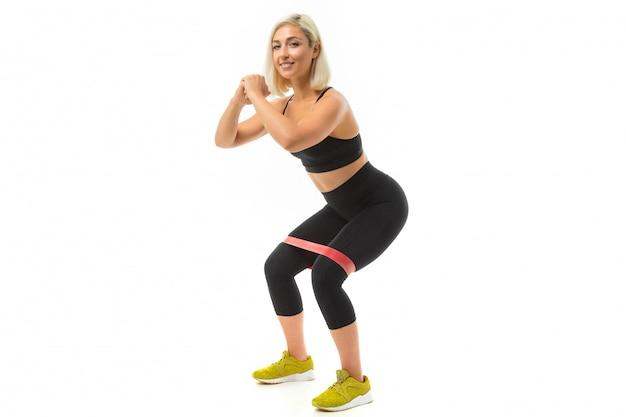 Sport fille caucasienne faire du sport avec élastique pour la forme physique et secoue les muscles des jambes isolés