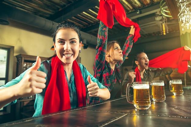 Sport, gens, loisirs, amitié, concept de divertissement - heureux fans de football ou bons jeunes amis buvant de la bière, célébrant la victoire au bar ou au pub. concept d'émotions positives humaines