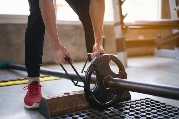Sport homme exercice d'entraînement avec haltère dans la salle de gym