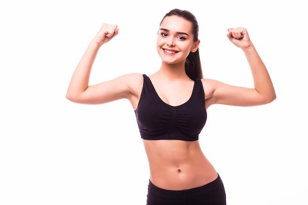 Sport jeune femme avec un corps parfait montrant les biceps, studio de fille de remise en forme tourné sur fond blanc