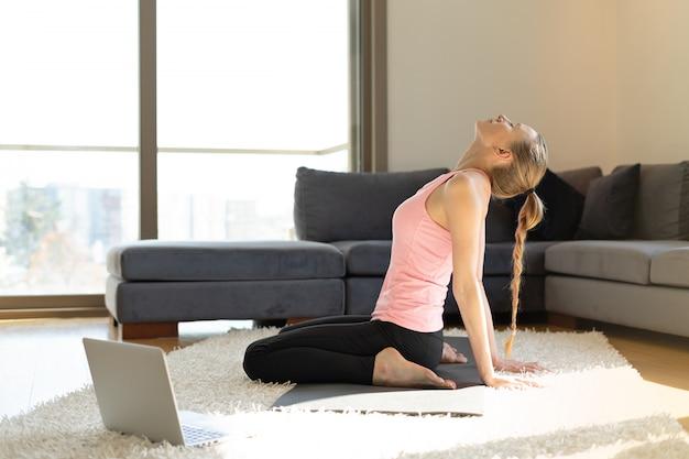Sport en ligne. jeune femme, faire, exercices, sur, natte yoga, ordinateur portable opposé