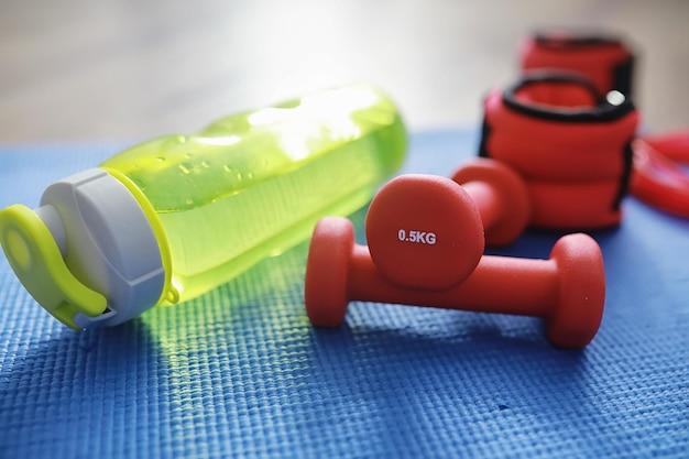 Sport et mode de vie sain. accessoires pour le sport. tapis de yoga haltère et corde à sauter. contexte sportif avec concept d'exercices à domicile.