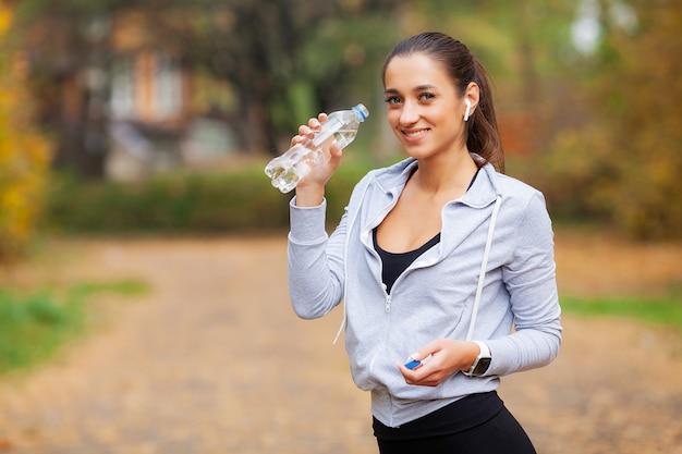 Sport en plein air. femme buvant de l'eau après avoir couru