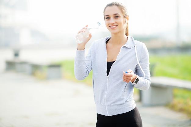 Sport en plein air. femme sportive dans les écouteurs de l'eau potable
