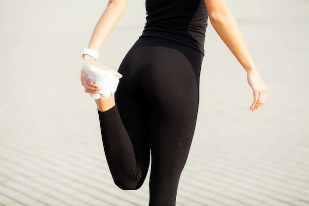 Sport en plein air. jeune fille fitness faisant des squats à l'extérieur en été