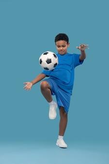 Sport préféré. garçon persistant à la peau foncée en short et t-shirt lançant un ballon de football avec le genou sur fond bleu