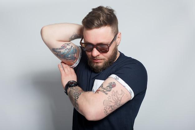 Sport, santé, personnes, concept 4k et style de vie - mode portrait de jeune homme barbu. souriant hipster boy.handsome man in hat.brutal garçon barbu avec tatouage