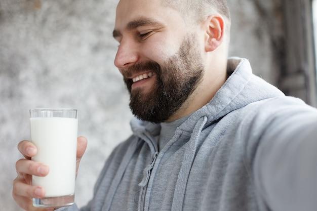Sport, santé, personnes, émotions, concept 4k et style de vie - un jeune homme boit et lèche la moustache blanche. jeune homme boit un peu de smoothie de crème fouettée reste sur son visage après avoir fini de boire