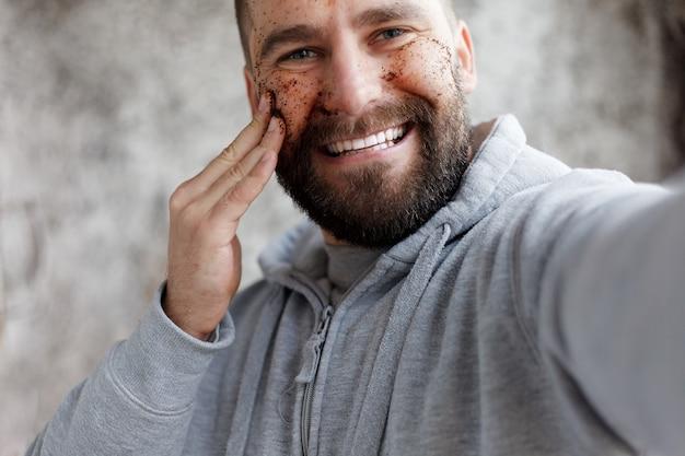 Sport, santé, personnes, émotions, concept de style de vie - bel homme avec trois masques différents masques au chocolat, à la crème et à l'argile. photo d'un homme à la peau parfaite. se toiletter