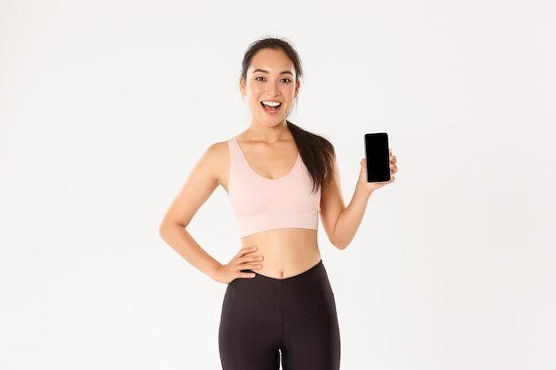 Sport, technologie et concept de mode de vie actif. sportive asiatique joyeuse excitée, coureuse montrant son meilleur score de course dans l'application smartphone, montre l'écran du téléphone portable avec l'application d'entraînement.