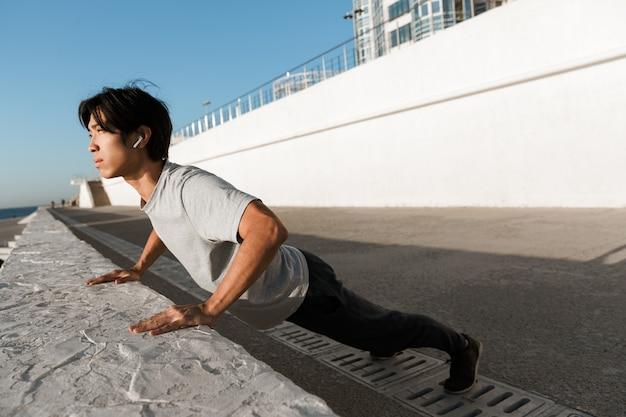 Sportif asiatique confiant en forme faisant des pompes au bord de la mer