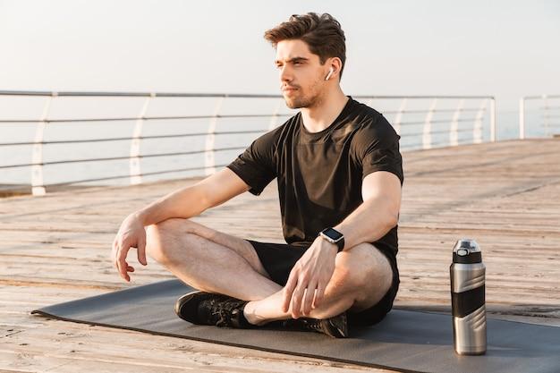 Sportif assis à l'extérieur avec une bouteille d'eau