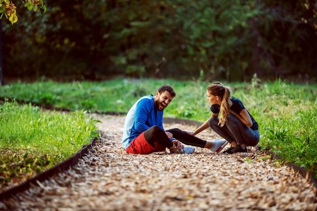 Sportif assis sur une piste dans les bois et tenant sa cheville blessée pendant que sa copine inquiète s'accroupit et l'aide.