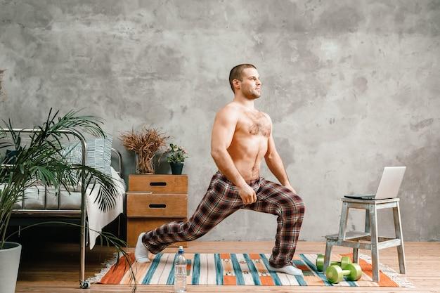 Un sportif aux cheveux noirs en pyjama à domicile fait des exercices du matin