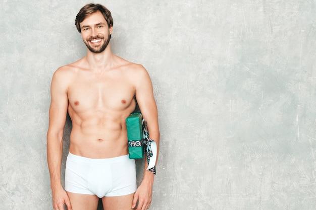 Sportif bel homme fort. modèle de remise en forme athlétique sain posant près d'un mur gris en sous-vêtements blancs.