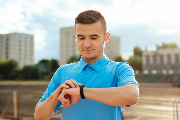Sportif, bel homme regardant et vérifiant sa montre après avoir couru dehors