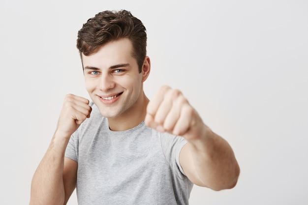 Sportif caucasien musclé confiant aux cheveux noirs vêtu d'une chemise grise tenant les poings devant, va se battre et se défendre. beau mec européen prêt à relever des défis montrant sa force