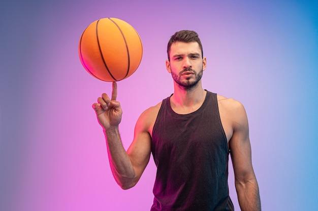 Sportif confiant filant le ballon de basket sur le doigt. jeune joueur de basket-ball européen barbu regardant la caméra. isolé sur fond bleu et rose. tournage en studio. espace de copie