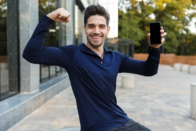 Sportif confiant montrant un téléphone mobile à écran vide à l'extérieur