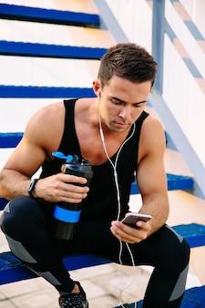 Sportif confiant musculaire dans le casque tenant une bouteille d'eau et en utilisant un téléphone mobile