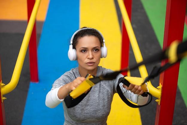 Sportif dans les écouteurs faisant des pull-ups sur des bretelles athlétiques