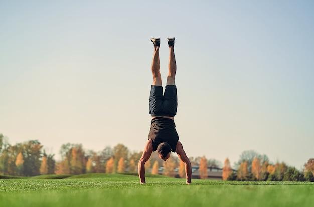 Le sportif debout sur les mains sur l'herbe