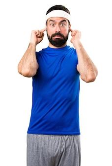 Sportif drôle couvrant ses oreilles sur fond blanc isolé