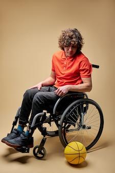 Sportif a dû abandonner le sport en raison d'un handicap, il est assis sur un fauteuil roulant, regardant la balle avec une expression triste sur le visage.