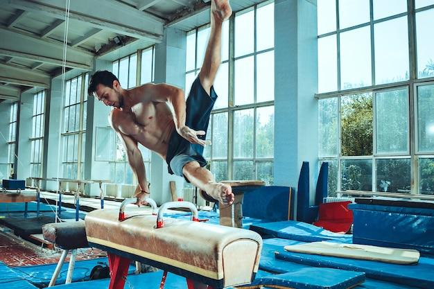 Le sportif effectuant un exercice de gymnastique difficile au gymnase