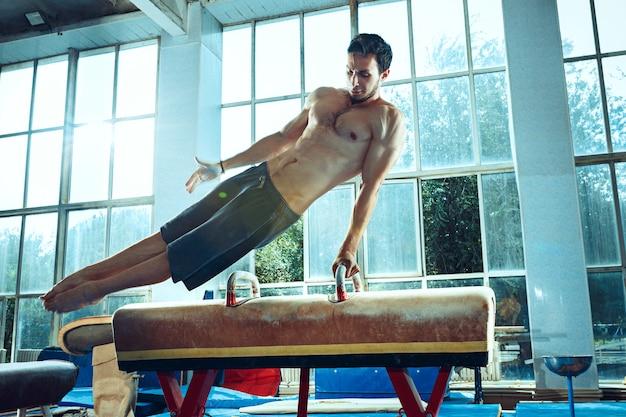 Le sportif effectuant des exercices de gymnastique difficiles au gymnase. le sport, l'exercice, le gymnaste, la santé, l'entraînement, le concept d'athlète. modèle de forme caucasienne