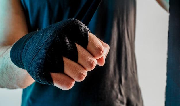 Sportif enveloppant un bandage de boxe sur le bras. vue rapprochée. isolé sur fond turquoise. prise de vue en studio