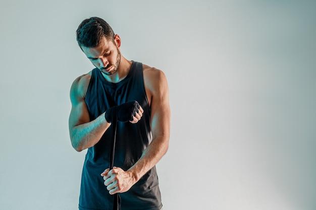 Sportif enveloppant un bandage de boxe à portée de main. un jeune boxeur européen barbu porte un uniforme de sport. isolé sur fond turquoise. tournage en studio. espace de copie