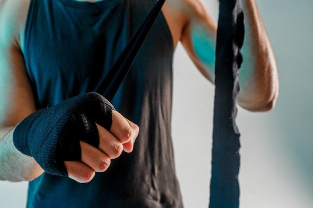 Sportif enveloppant un bandage de boxe à portée de main. vue rapprochée. isolé sur fond turquoise. prise de vue en studio