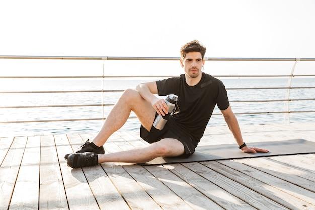 Sportif à l'extérieur assis avec une bouteille d'eau